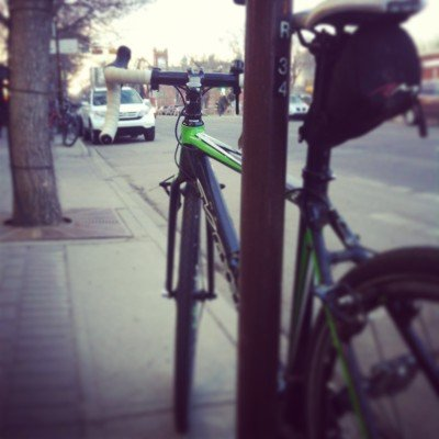 A bicycle commuting. Locked to a parking meter in Old Strathcona, Edmonton.